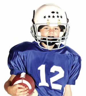 Kid playing football an athletic mouth guard