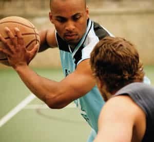 Men playing basketball with mouth guards